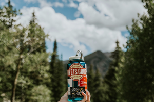 A reusable water bottle being held in front of mountains.