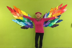 Photo of Professor April Allen standing in front of an art installation of multicolored wings