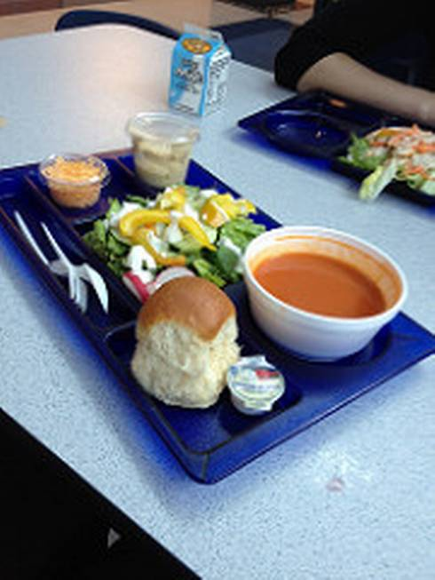 School lunch with roll, soup, salad, cheese, and milk.