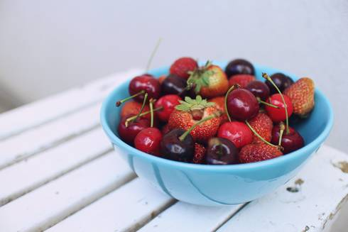 Blue bowl filled with strawberries and cherries.