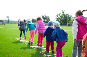 Children in a row hopping over a ladder on a field.