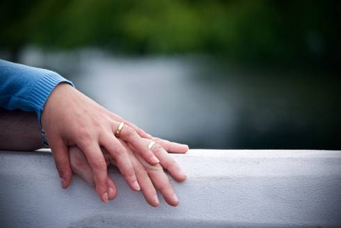 A couples hands resting on a gray surface
