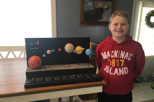 Brady Gibson with a display of the solar system.