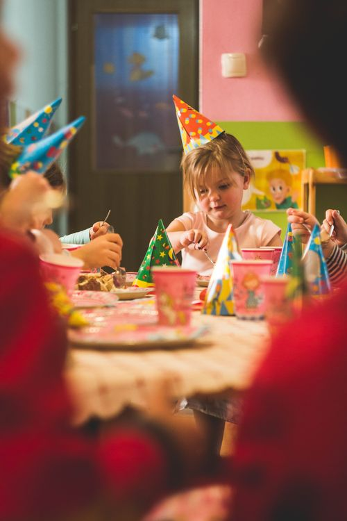 Girl celebrating her birthday in a classroom with party hat on.