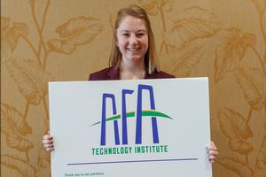 Sarah Lokey holding a sign that reads AFA Technology Institute