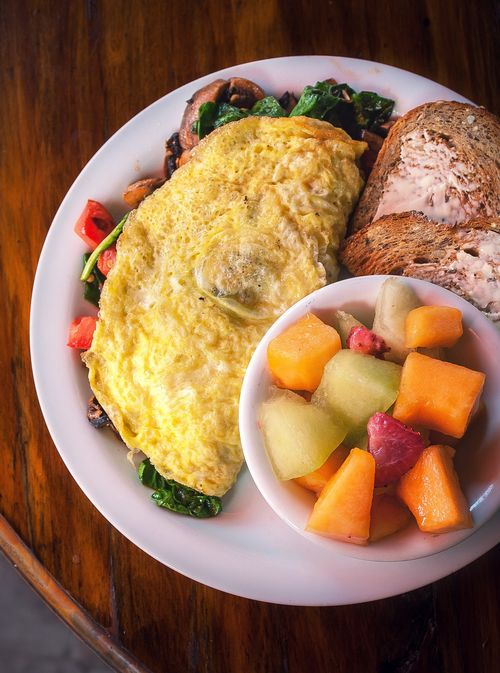 Omelet with bread and fresh fruit on a plate.