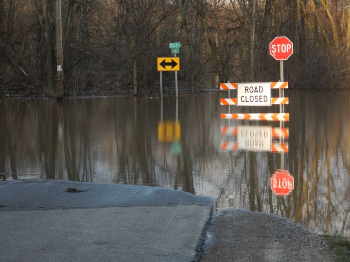 Water is shown covering a road. Road closed sign warns drivers not to enter the roadway.