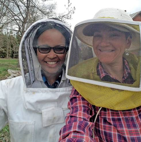 Women wearing beekeeper face nets