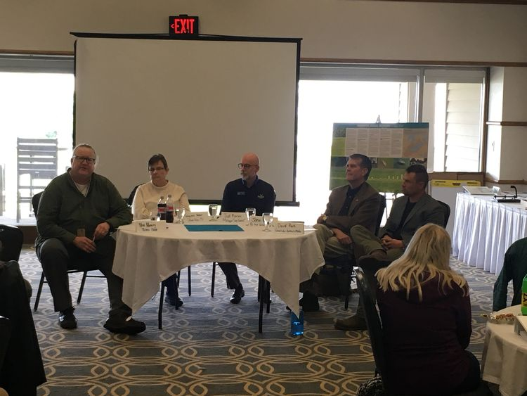 Five people representing science communicators sit around half of a round table facing a group as part of a discussion panel on science communication.