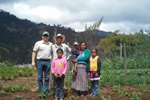 MSU researcher poses with a Guatemalan family in one of their bean fields
