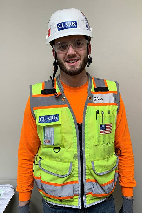 Photo of Jack Brierton wearing construction hard hat and vest.