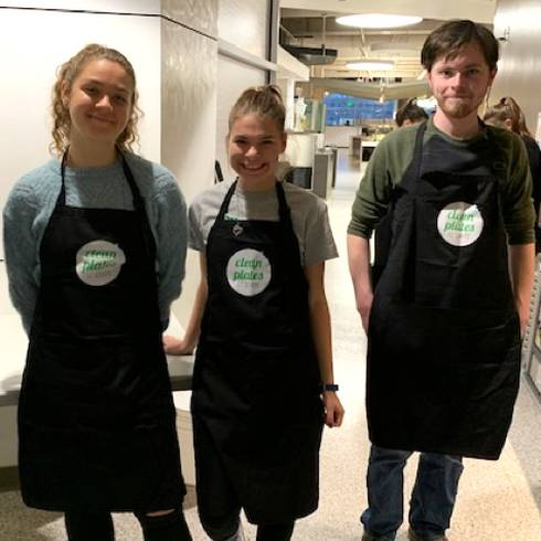 MSU students, two female and one male, in black aprons