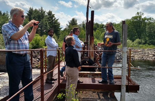 Photo of MSU and MDHHS standing on a dam in the Upper Peninsula, with officials from Marquette County discussing water fluctuation levels of the river.