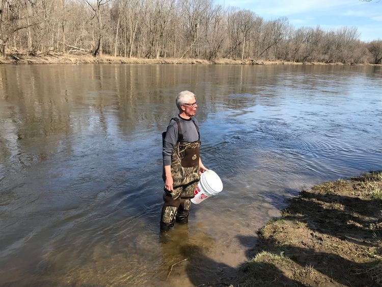St. John's Lutheran School teacher Mark Koschmann stands in a river wearing waders and holding a pail in his hand.