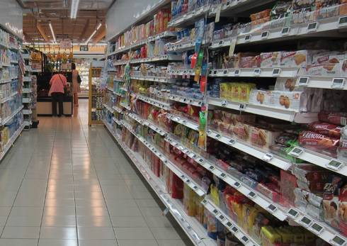 Grocery store aisle with shelves full of processed foods