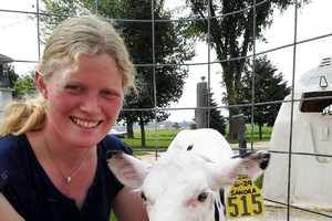 2015 International Youth Exchange participant Sandra Wefer from Germany with a calf born during her stay with one of her Michigan host families.