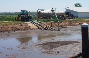 Tractor pumping out of a manure lagoon.