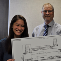 In April 2019, Gary McDowell, director of Michigan Department of Agriculture and Rural Development, visited Michigan State University for an update on the mobile food processing labs development and the on-campus fruit and vegetable lab renovations. McDowell (center) reviewed the mobile lab design concepts plans with students Lauren Kitada (left) and Katie Church at the meeting.