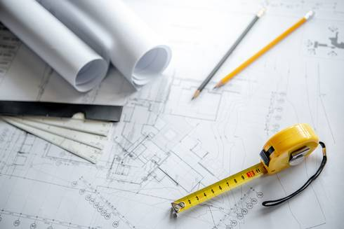 tape measure, pencils and rulers on schematics and blueprints