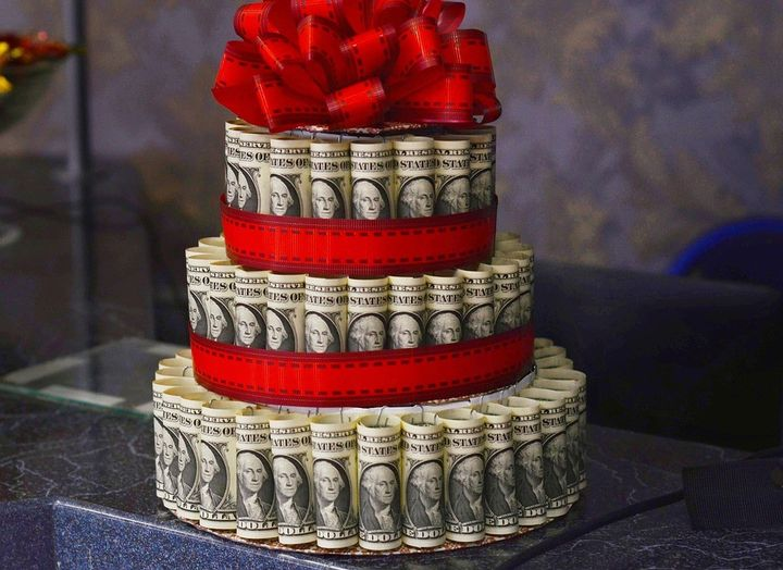layered rolled dollar bills topped with a ribbon bow.