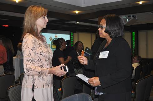 Sandra Walker talks with an audience member after Food@MSU's Our Table conversation on food safety in May 2018.
