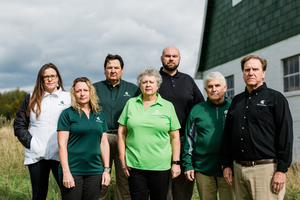 Members of the MSU Extension farm stress team pose in front of a farm.