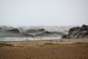 A view from a sandy beach on Lake Michigan looking out over the high waves and whitecaps during a storm.