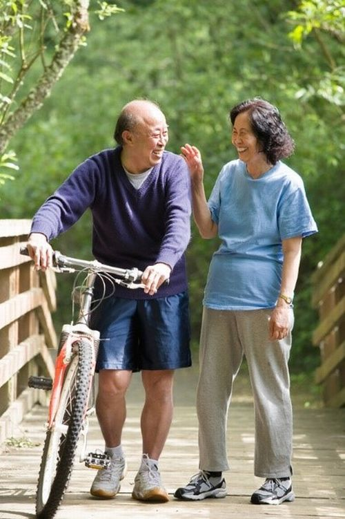 An older couple smiling while walking a bicycle over a bridge.