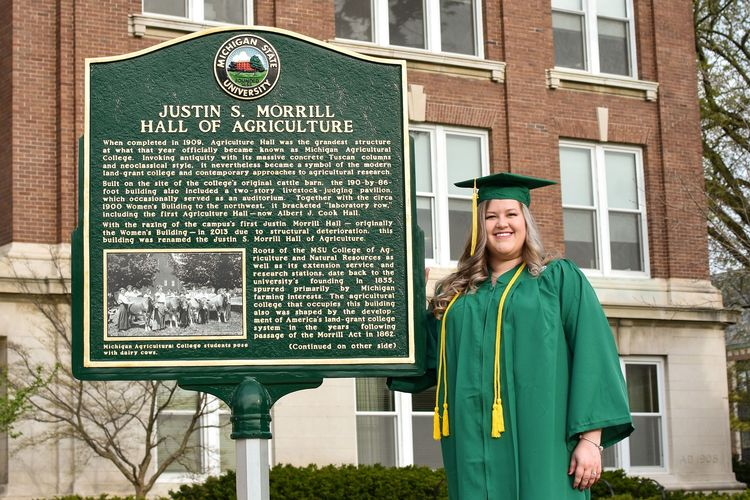Michigan State University student Lauren Heberling outside of Morrill Hall of Agriculture on campus in her graduation cap and gown.