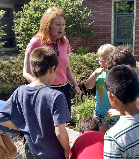 Master Gardener trainee, Liz Slajus, directs childcare students to observe and taste test the lettuce they are growing. Photo by Rebecca Krans, MSU Extension