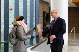 CANR Dean Ron Hendrick gives a student a Snacks for Success bag as she leaves an exam.