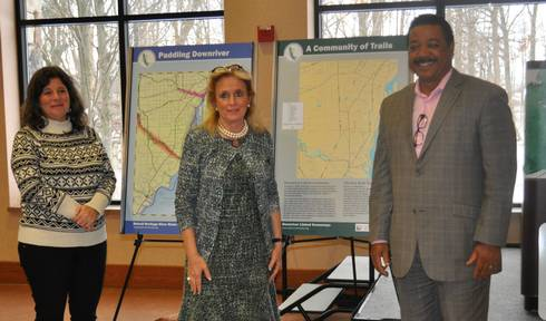From left, Tiffany Van DeHey, owner Riverside Kayak Connection; Congresswoman Debbie Dingell; and Richard Marsh, city manager River Rouge stand in front of three sign kiosks that will be installed in 11 locations along the Downriver Linked Greenways. Photo credit: Friends of the Detroit River