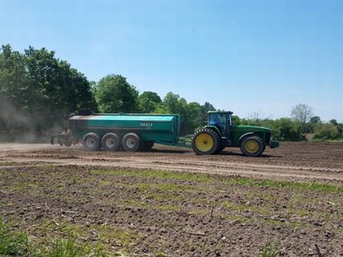 A tractor pulls a container spreading manure in a field.
