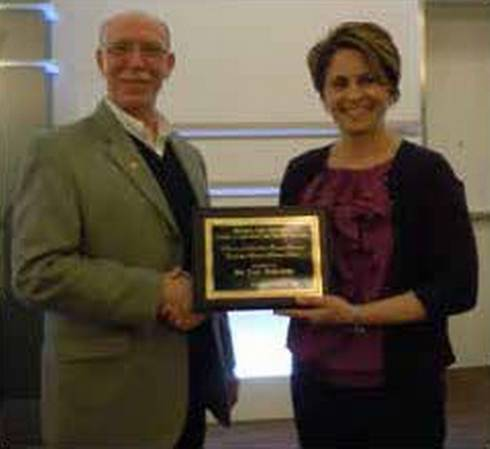 Photo of Paul Nieratko receiving the 2013 Howard and Lili Camden Teacher/Scholar Award from Dr. Kelly Millenbah.