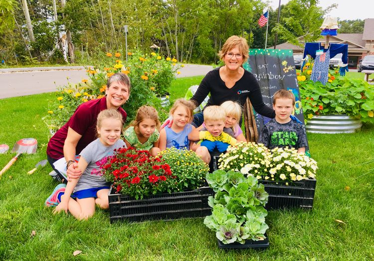 Kendra Gibson poses with a group of students in front of a garden box.