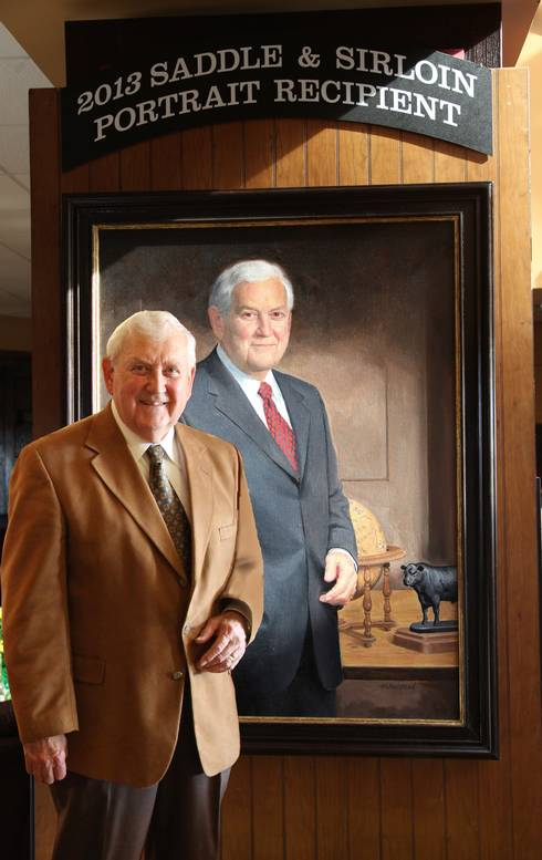 Hawkins, standing in front of his portrait that was made part of the prestigious Saddle & Sirloin Portrait Collection.