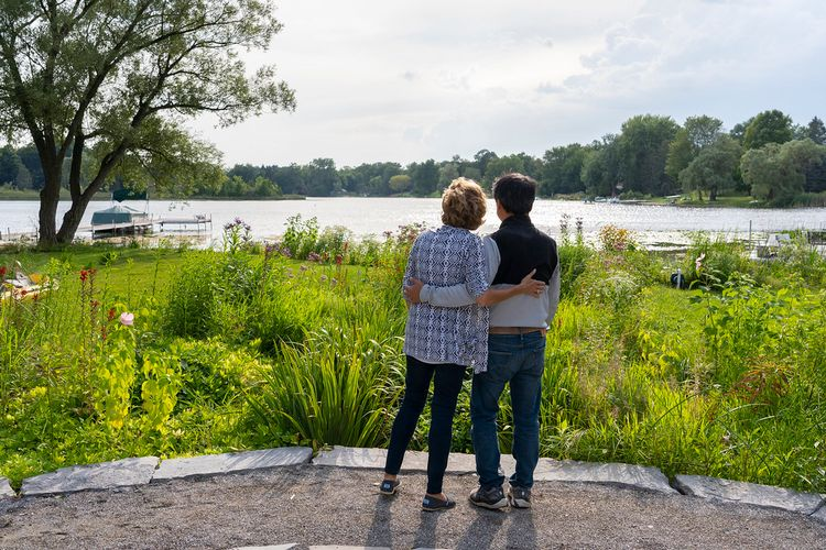 A man and woman with arms wrapped around each other looking out at a lake.