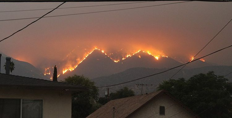 Fire in mountains in the distance with houses in the foreground.