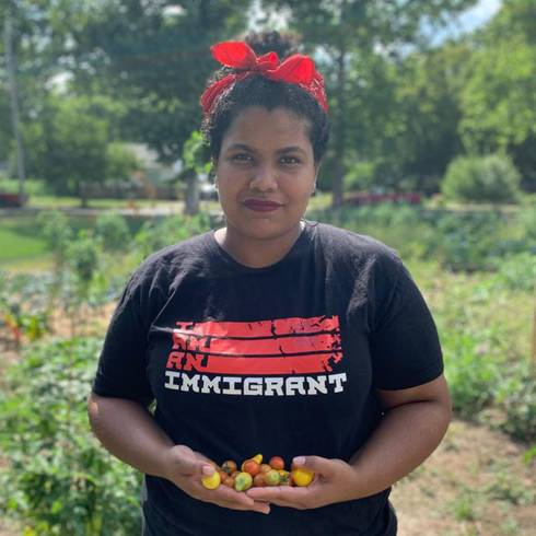 Vanessa holds colorful cherry tomatoes in her hands. She is wearing a shirt that says,