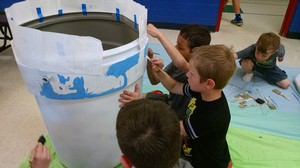 Youth paint a rain barrel recently. Sketching your design first on a sheet of paper can help the painting process. The rain barrels will be on display around Bay County in August. Photo: Michigan Sea Grant