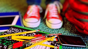 A pair of youth sneakers with notebooks, pencils, pens and other back to school supplies.