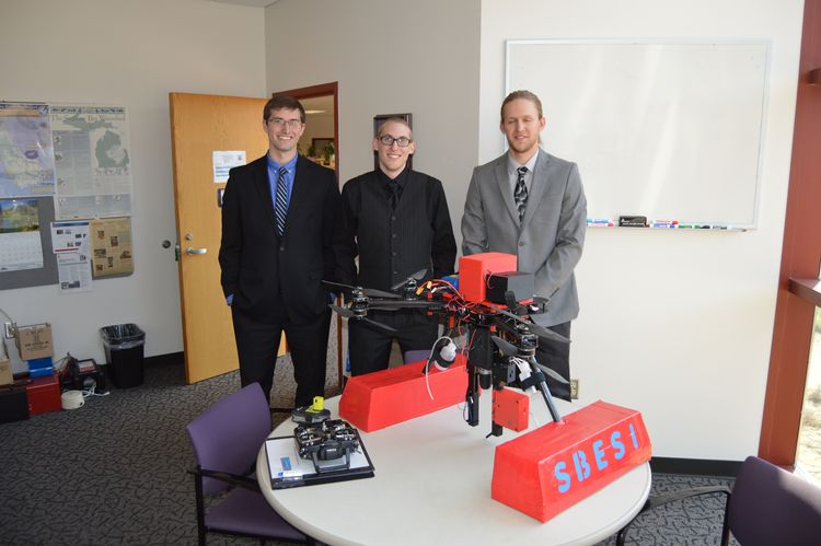 Saginaw Valley State University students Carson Beauchaine, Chris Rush, and Justin Krenzke stand with the water sampling UAV they built. Their adviser on the project Professor Thomas Kullgren is not pictured. Photo credit: David Karpovich