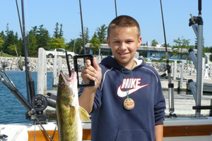 Young boy holds up walleye while standing on a boat.