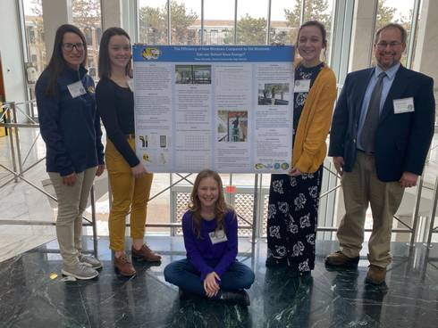 Three students and two adults who participated in the symposium are shown standing and sitting near a display of the student posters that describes their research.