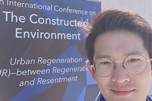 Image of Juntae Jake Son in front of The Constructed Environment Conference sign.