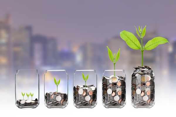 mix coins and seed in clear bottle on cityscape photo blurred cityscape background,Business investment growth concept