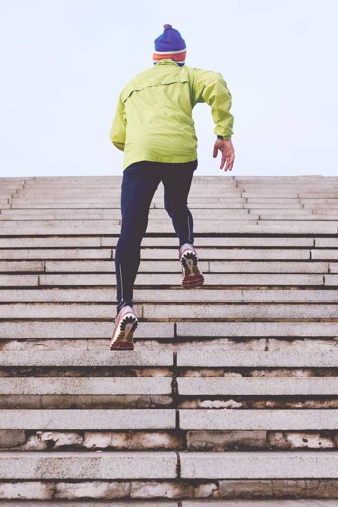 Man exercising by running up stone steps.