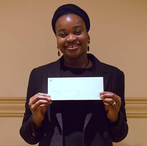 Image of Najma holding a white envelope containing her scholarship.