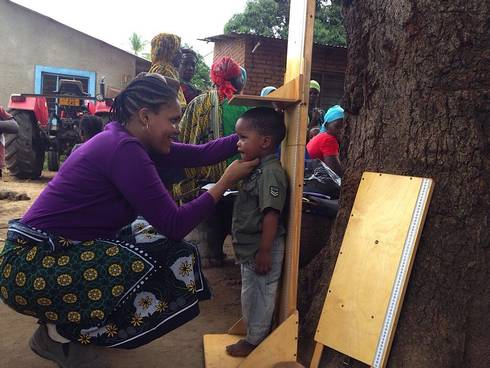 Theresia Jumbe collects height data from a child in Tanzania.