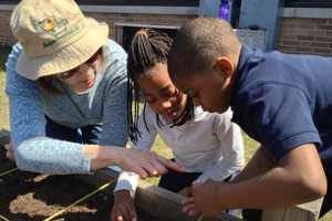 The Coalition for Community Development helps students at MLK Elementary plant carrots. Photo courtesy of cffmc.org.